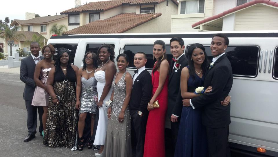 several young adults in formal wear standing next to stretch limousine hummer h2 from A Plus Limos