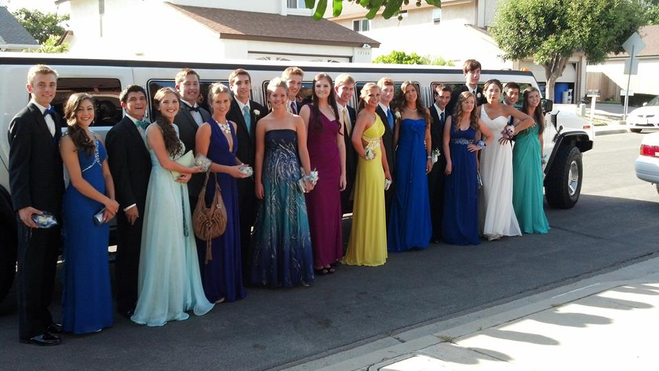 several young couples in formal wear standing with white hummer limo from A Plus Limos