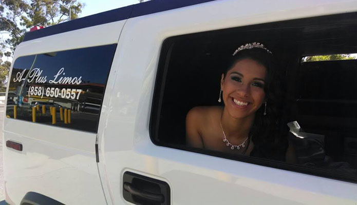 young woman dressed in formal gown looking out a window of a white hummer limousine